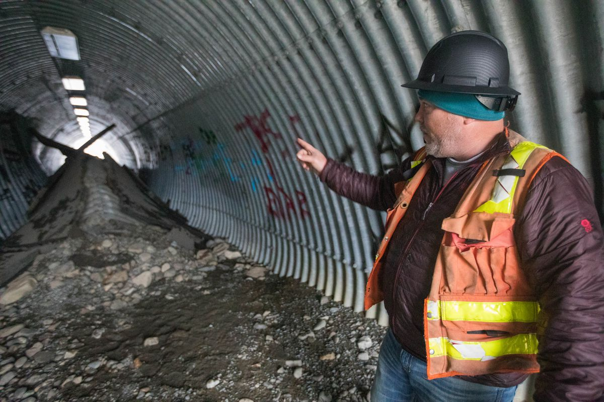 DOT project engineer Jason Baxley points out damage to a pedestrian underpass beneath Eagle River Loop Road on Saturday, Dec. 1, 2018. During the Friday morning earthquake, an 8 inch water main broke, causing the damage to the underpass. (Loren Holmes / ADN)