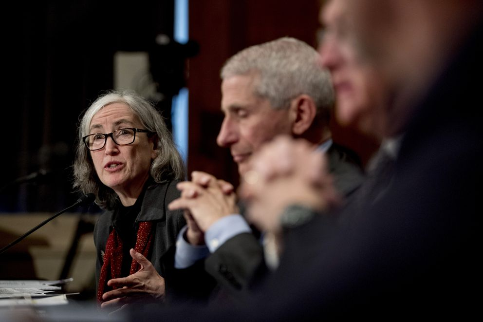 FILE - In this March 3, 2020, file photo, Centers for Disease Control and Prevention Principal Deputy Director Anne Schuchat, left, accompanied by National Institute for Allergy and Infectious Diseases Director Dr. Anthony Fauci, right, testifies before a Senate Health, Education, Labor and Pensions Committee hearing on the coronavirus on Capitol Hill in Washington. In the United States, the nation with the most pandemic deaths, the reporting of vital coronavirus case and testing data is not keeping pace with its speedy spread. Public health officials nationwide lean too heavily on faxes, email and spreadsheets, sluggish and inefficient 20th-century tools. (AP Photo/Andrew Harnik, File)