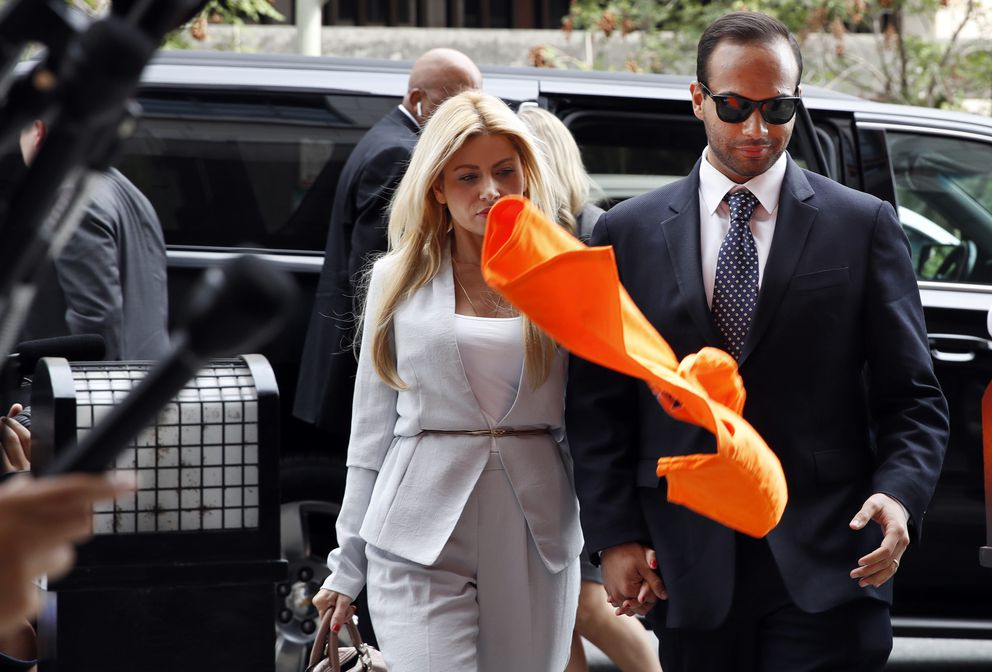 An orange shirt saying 'inmate ' is thrown by a protester at former Donald Trump presidential campaign foreign policy adviser George Papadopoulos, right, who triggered the Russia investigation, and who pleaded guilty to one count of making false statements to the FBI, as he holds hands with his wife Simona Mangiante on arrival at federal court for sentencing, Friday, Sept. 7, 2018, in Washington. (AP Photo/Jacquelyn Martin)