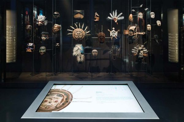 A display in the Smithsonian Arctic Studies Center allows visitors to use an interactive screen to get detailed views of the Native masks in the case before them. (Photo by Chuck Choi, courtesy of the Anchorage Museum)