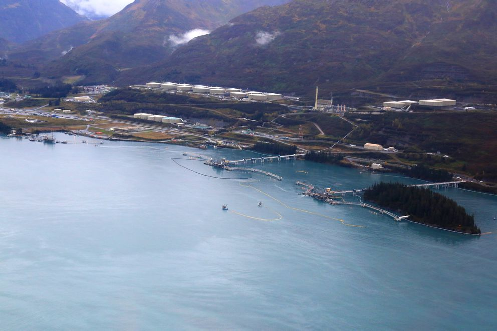 Response personnel work to contain and collect rainbow sheen near the Valdez Marine Terminal on Saturday. Yellow containment boom is used to concentrate oil so it can be picked up. (Courtesy Alyeska Pipeline Service Co.)