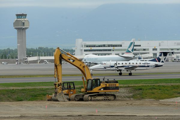 An ACE Air Cargo plane taxies past construction equipment after landing on the east west runway at Ted Stevens International Airport in Anchorage, AK on Friday June 22, 2018. (Bob Hallinen / ADN)