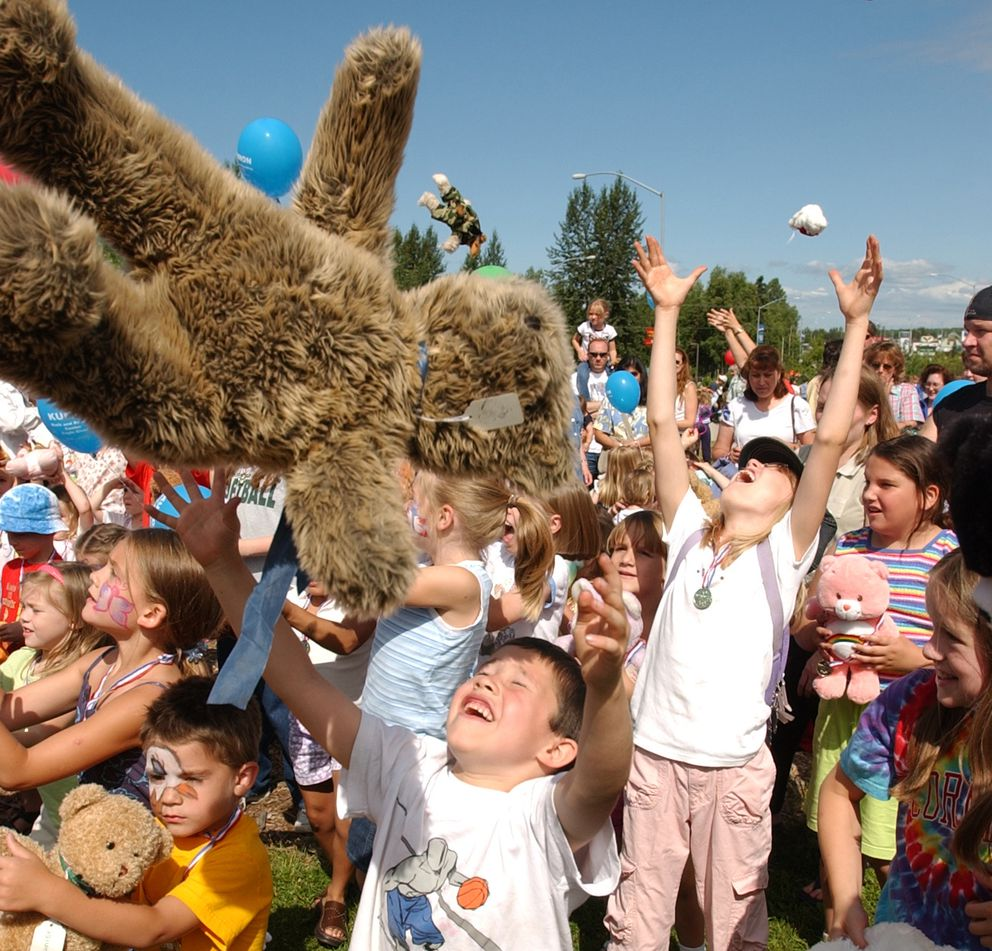 """Teddy Bears go airborne as Keston Carter, 6, center, and others launch their stuffed toys on cue while listening to the song """"Teddy Bear's Picnic"""" at the Teddy Bear Picnic and Family Fun Day Friday at the Bear Paw Festival in Eagle River. A short parade of owners and critters followed.(Erik Hill/Anchorage Daily News)"""