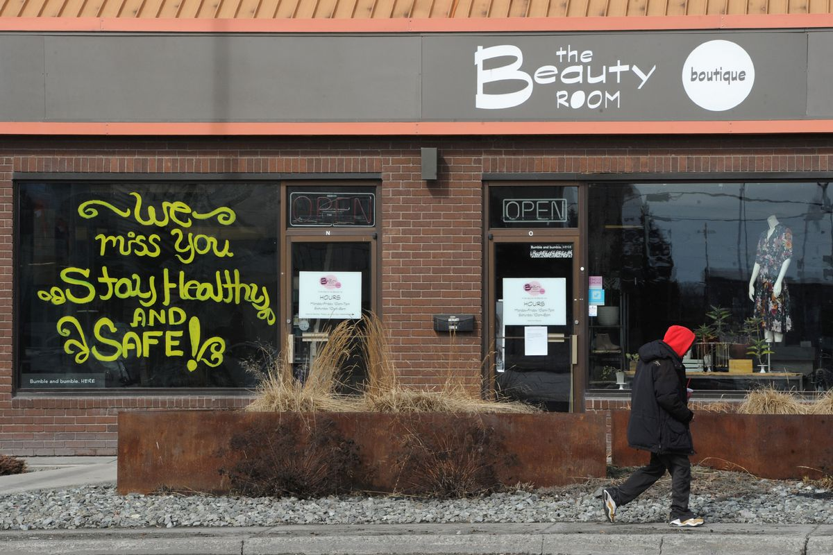 A pedestrian walks past the Beauty Room day spa & beauty boutique on Northern Lights Boulevard with a note to customers while the business remained closed on Monday, April 13, 2020, during the COVID-19 pandemic. (Bill Roth / ADN)