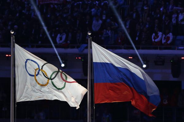 FILE - In this Feb. 23, 2014 file photo the Russian national flag, right, flies after it is hoisted next to the Olympic flag during the closing ceremony of the 2014 Winter Olympics in Sochi, Russia. The ruling on whether Russia can keep its name and flag for the Olympics will be announced on Thursday Dec. 17, 2020. The Court of Arbitration for Sport said Wednesday that three of its arbitrators held a four-day hearing last month in the dispute between the World Anti-Doping Agency and its Russian affiliate, known as RUSADA. (AP Photo/Matthias Schrader, file)