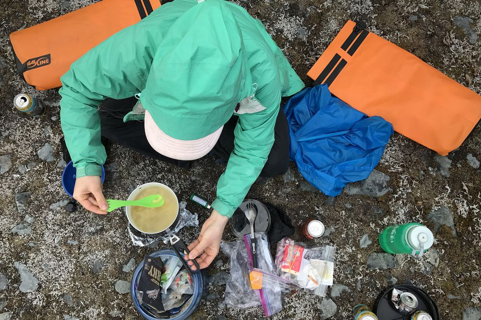 Devin Kelly prepares pasta with reindeer sausage, white cheddar and red onion at a campsite near Spencer Glacier on Sunday, June 11, 2017. (Vicky Ho / Alaska Dispatch News)