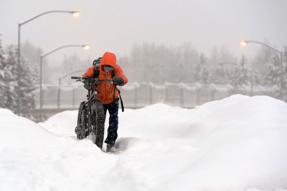 Gunnar Evensen walks his bicycle up an unplowed sidewalk along West Northern Lights Boulevard on Monday afternoon in West Anchorage. (Erik Hill / Alaska Dispatch News)