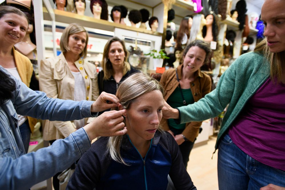 With support from friends, Kikkan Randall tries on wigs at Fashion Wigs in the Northway Mall on July 13, 2018. From left are Diana Johnson, Nicole DeYong, Kristy DeYong, Rachel Samuelson and Laura Gardner. (Marc Lester / ADN)