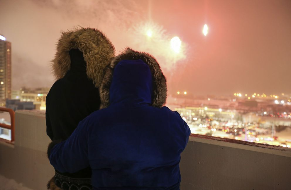 Ada Coyle and Walter Savetilik watch the AT&T Fireworks Extravaganza during Fur Rendezvous from the parking garage on W. Fifth Avenue in downtown Anchorage on Saturday, Feb. 27, 2021. (Emily Mesner / ADN)