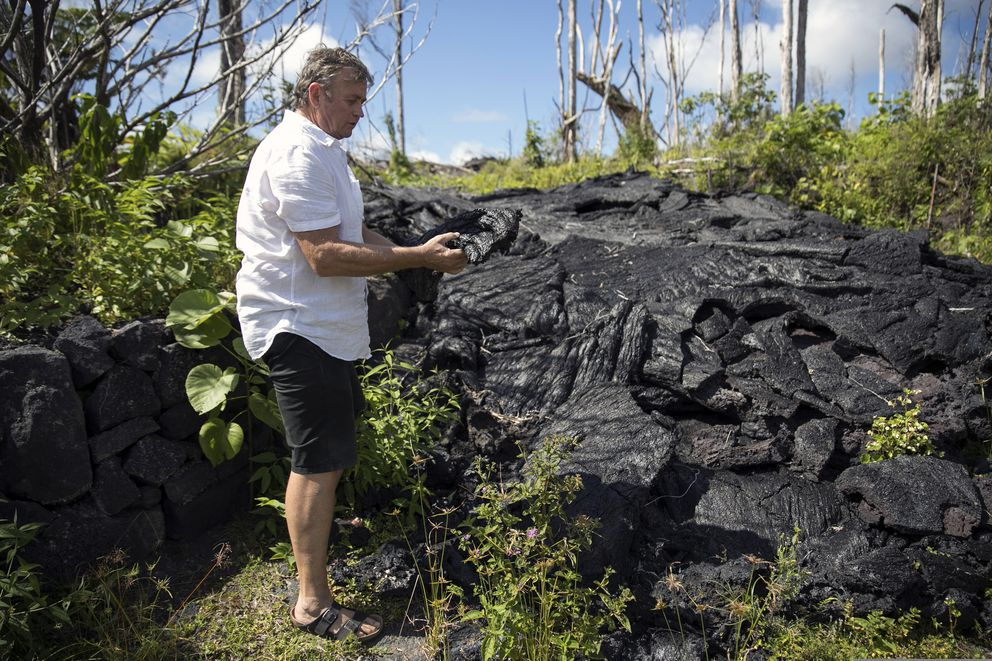 In this Tuesday, April 23, 2019 photo, Leilani Estates resident Mark Figley stands in front of the 2018 Kilauea eruption that stopped short of overtaking his home near Pahoa, Hawaii. While his home was spared by the eruption, noxious volcanic gases have made it unlivable. So, for now, the home on the edge of a lava flow remains vacant as Figley settles into his new Big Island home, a little farther away from Kilauea volcano. (AP Photo/Marco Garcia)