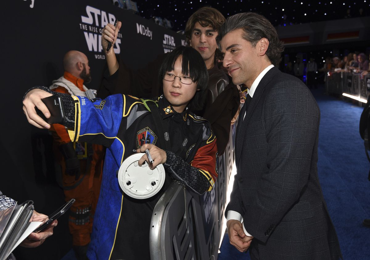 Oscar Isacc, right, takes a selfie with a fan as he arrives at the world premiere of