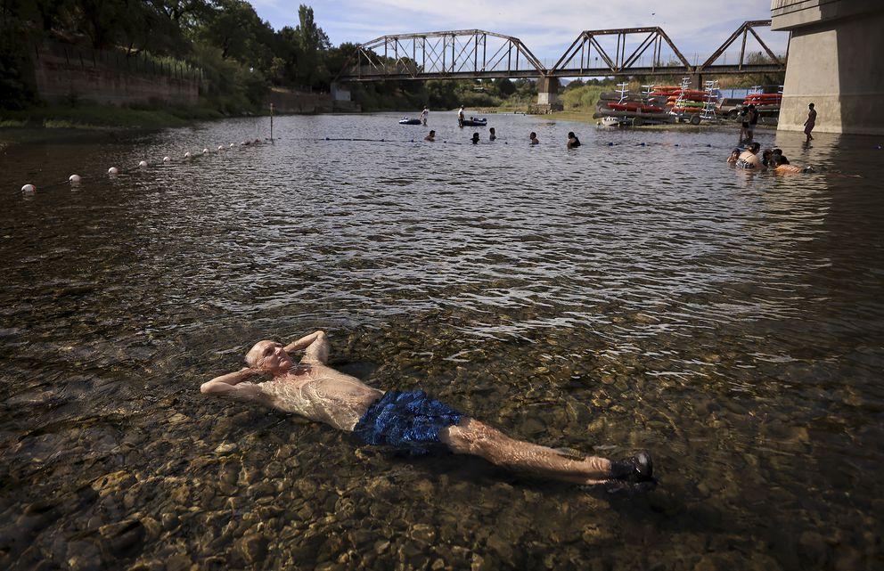 Gerry Huddleston of Santa Rosa, Calf. cools off in the very shallow water of the Russian River, Wednesday, June 16, 2021 at the Veterans Memorial Beach in Healdsburg, Calif. (Kent Porter/The Press Democrat via AP)