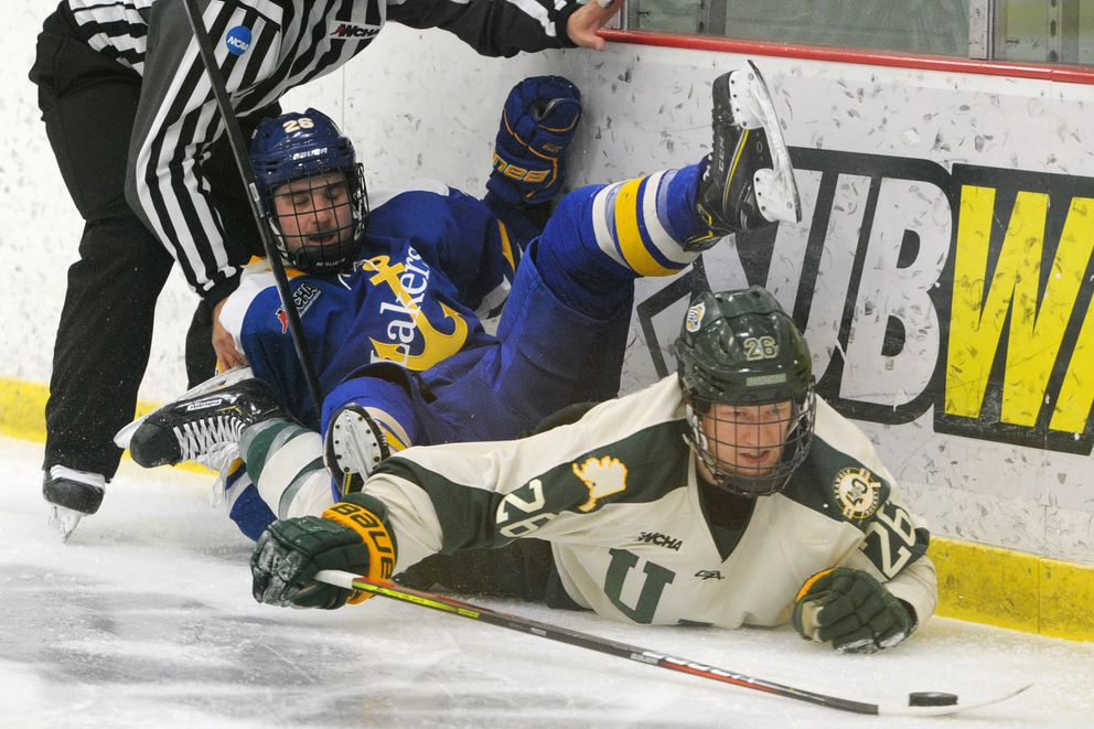 Lake Superior State forward Pete Veillette and UAA defenseman Aaron McPheters crash into the boards during the Seawolves' 5-3 loss Sunday. (Bill Roth / ADN)