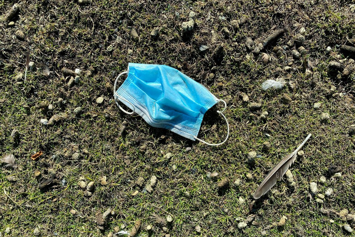 A discarded face mask lies on the ground Tuesday, July 14, 2020 at the Alaska Native Medical Center. (Loren Holmes / ADN)