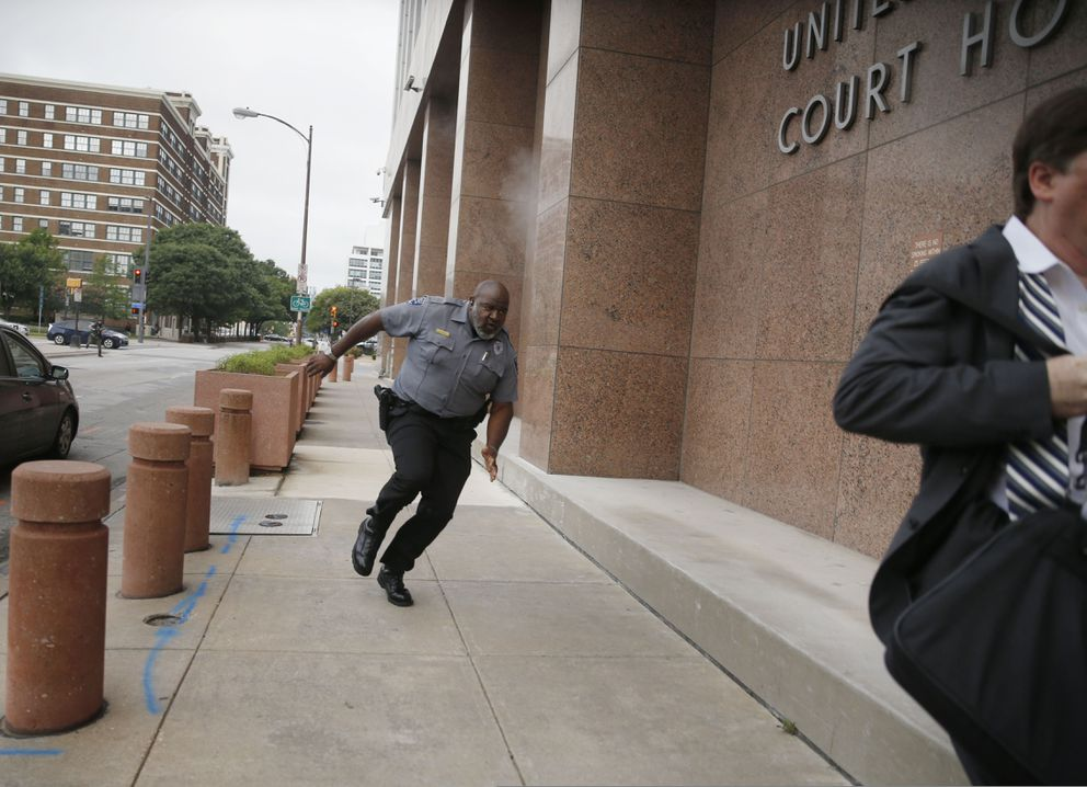A security guard and a civilian run for cover as bullets ricochet off the building as a shooter (far background left) fires towards them on Monday, June 17, 2019 at the Earle Cabell federal courthouse in Dallas. (Tom Fox/The Dallas Morning News via AP)