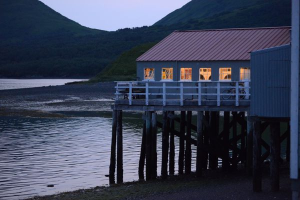 Lights come on in buildings as dusk takes hold at the Larsen Bay cannery, July 13, 2017. (Anne Raup / Alaska Dispatch News)