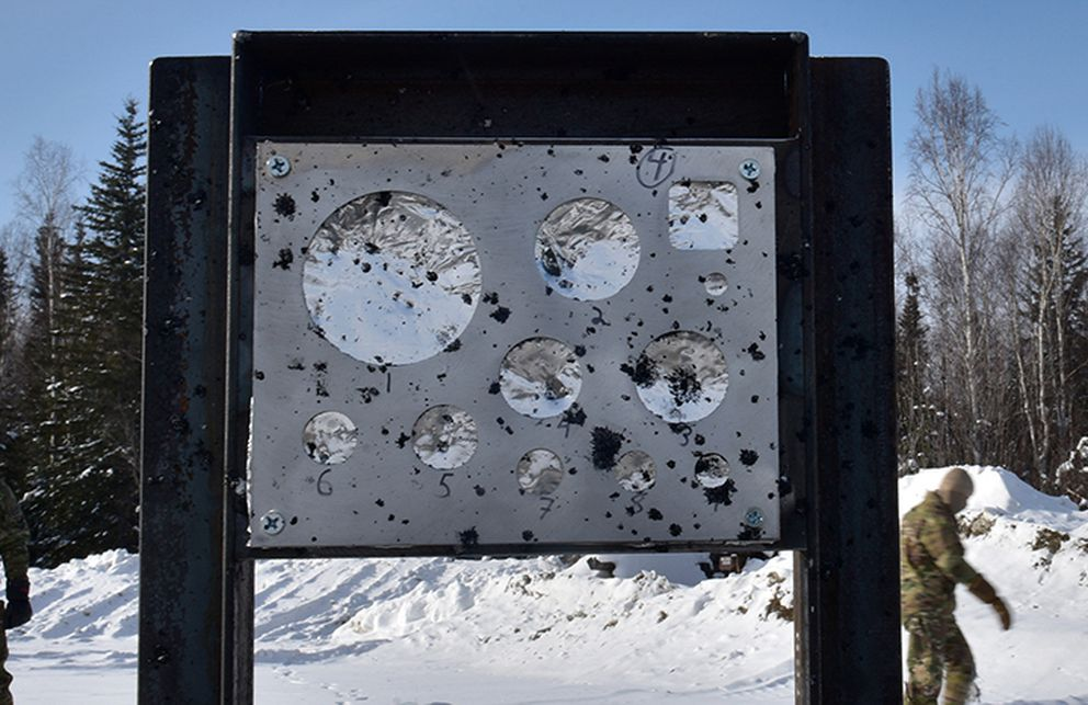U.S. Air Force Airmen from 354th Civil Engineer Squadron Explosive Ordnance Disposal (EOD) Flight inspect a gauge stand after a snow mitigation test March 18, 2021 at Eielson Air Force Base near Fairbanks. The foil held in the gauge stands is used to measure the blast overpressure caused by the explosion. (U.S. photo by Senior Airman Danielle Sukhlall)