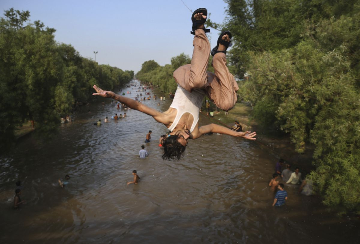A Pakistani jumps as people cool themselves off in a canal in Lahore, Pakistan. (AP Photo/K M Chaudhry)