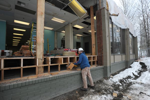 Carpenter Eric Dearen with Criterion General makes repairs to a commercial building at 3rd Avenue and Post Road on Monday, Nov. 18, 2019, that was damaged by the 7.1 earthquake nearly a year ago. (Bill Roth / ADN)