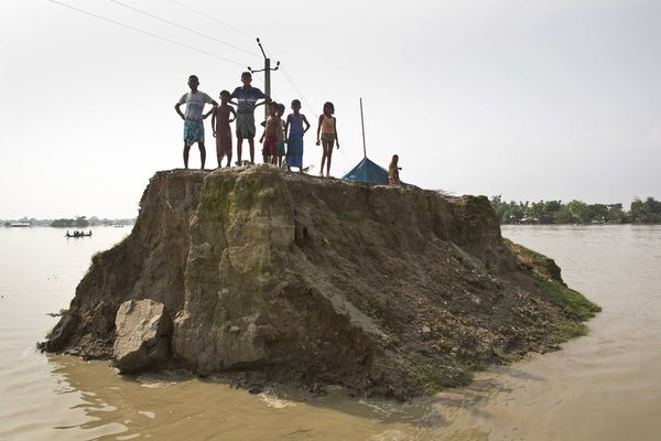 In this Aug. 15, 2017, file photo, flood-affected villagers wait for relief material on what's left of a road washed away by floodwaters in Morigaon district, east of Gauhati, northeastern state of Assam. Deadly landslides and flooding are common across South Asia during the summer monsoon season that stretches from June to September. (AP Photo/Anupam Nath, File)