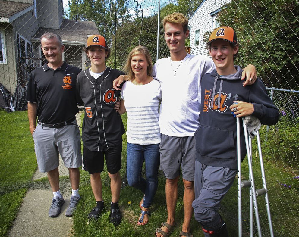 The Opinsky family, from left, John, Jack, Cathy, Jimmy and Nicko, stand inside the homemade batting cage at their Anchorage home. (Emily Mesner / ADN)