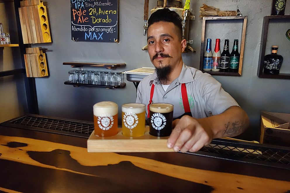 "Jorge, one of the brewers at ""La Santísima Flor de Lupulo,"" presents a flight of his draft beers (left to right): Pale Ale, White IPA, Black IPA. (Photo: Scott McMurren)"