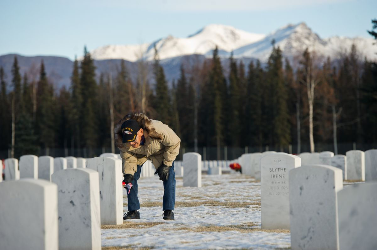 Howard Nunooruk Sr. places flowers on the gravesite of his brother Romeo Nanooruk at Fort Richardson National Cemetery on Veterans Day on Nov. 11, 2016. Romeo Nanooruk, who died in 1987, was a World War II veteran who fought in the Aleutian Islands campaign, according to Howard's son, Homer Nunooruk. (Marc Lester / ADN archive)