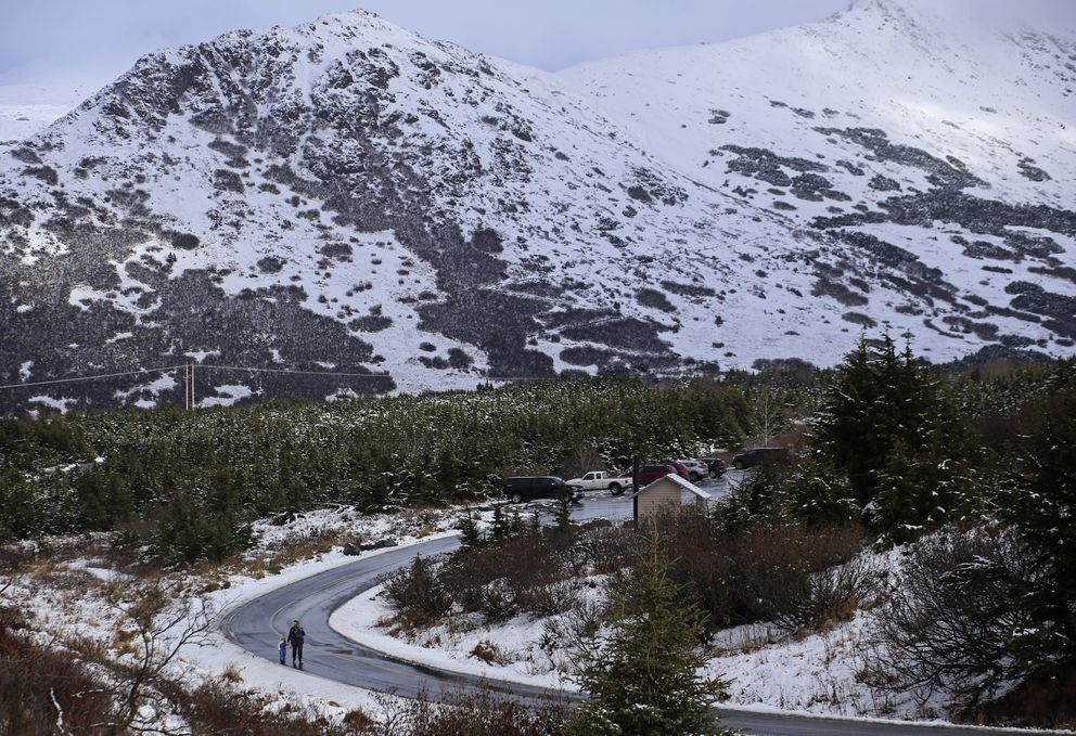 A woman walks with children from the lower parking lot at the Glen Alps parking area as fresh snow partially covers the ground and nearby mountains on Oct. 15, 2020. (Emily Mesner / ADN)