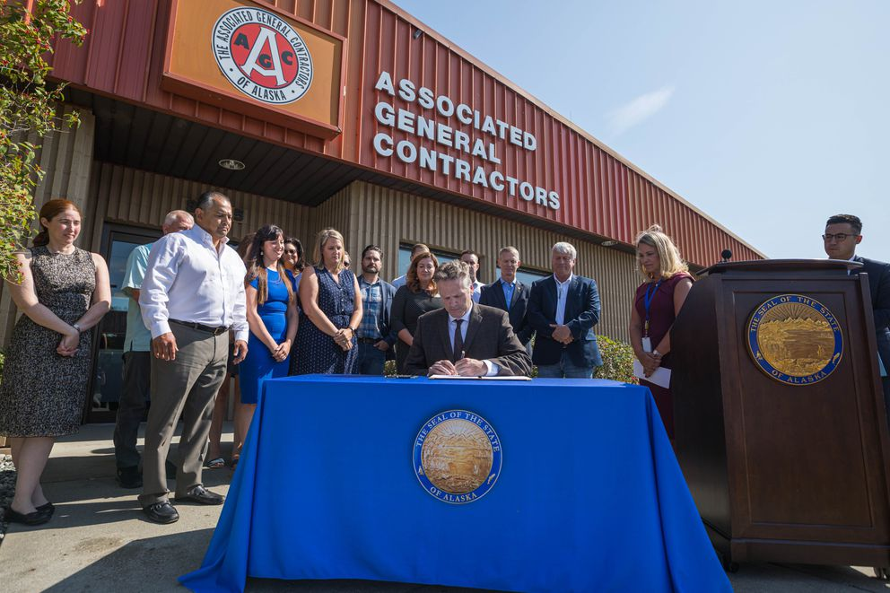 Gov. Mike Dunleavy signs Senate Bill 2002, which fixes the capital budget and reverse sweep, Thursday, Aug. 8, 2019 at the Associated General Contractors offices in Anchorage. (Loren Holmes / ADN)
