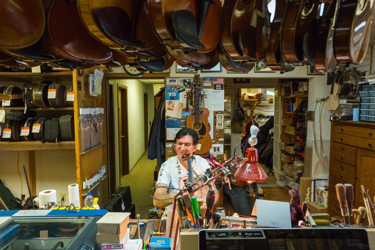 Petr Bucinsky adjusts the bridge of a violin at his violin shop on Tuesday, Aug. 30, 2016. (Loren Holmes / Alaska Dispatch News)