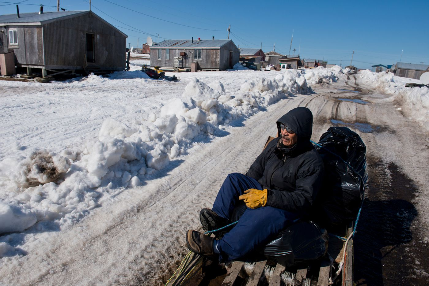 Roy Waghiyi catches a ride in a ATV-pulled sled to his home in Savoonga in April. (Marc Lester / Alaska Dispatch News)