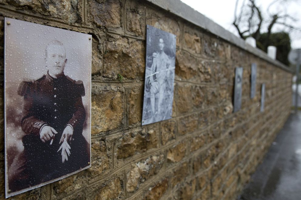 In this photo taken on Tuesday, Oct. 30, 2018, a photo of French WWI soldier Augustin Trebuchon hangs on a wall outside a cemetery in Vrigne-Meuse, France. Trebuchon is recorded as the last French soldier to die. Hundreds of troops died on the final morning of World War I _ even after an armistice was reached and before it came into force. Death at literally the 11th hour highlighted the futility of a conflict that had become even more incomprehensible in four years of battle. (AP Photo/Virginia Mayo)