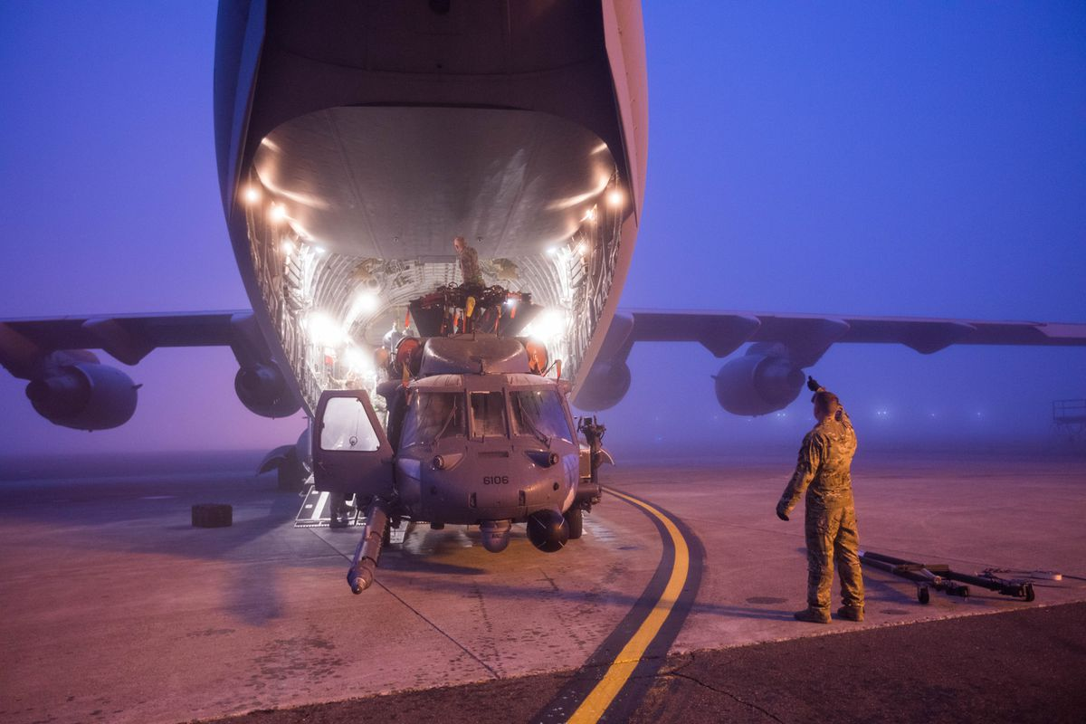 Guardsmen load a HH-60 Pave Hawk helicopter into a C-17 transport plane Tuesday, Sept. 26, 2017, at Joint Base Elmendorf-Richardson. The 210th Rescue Squadron, part of the Alaska Air National Guard 176th wing, is deploying to the Middle East on a combat search and rescue mission. (Loren Holmes / Alaska Dispatch News)