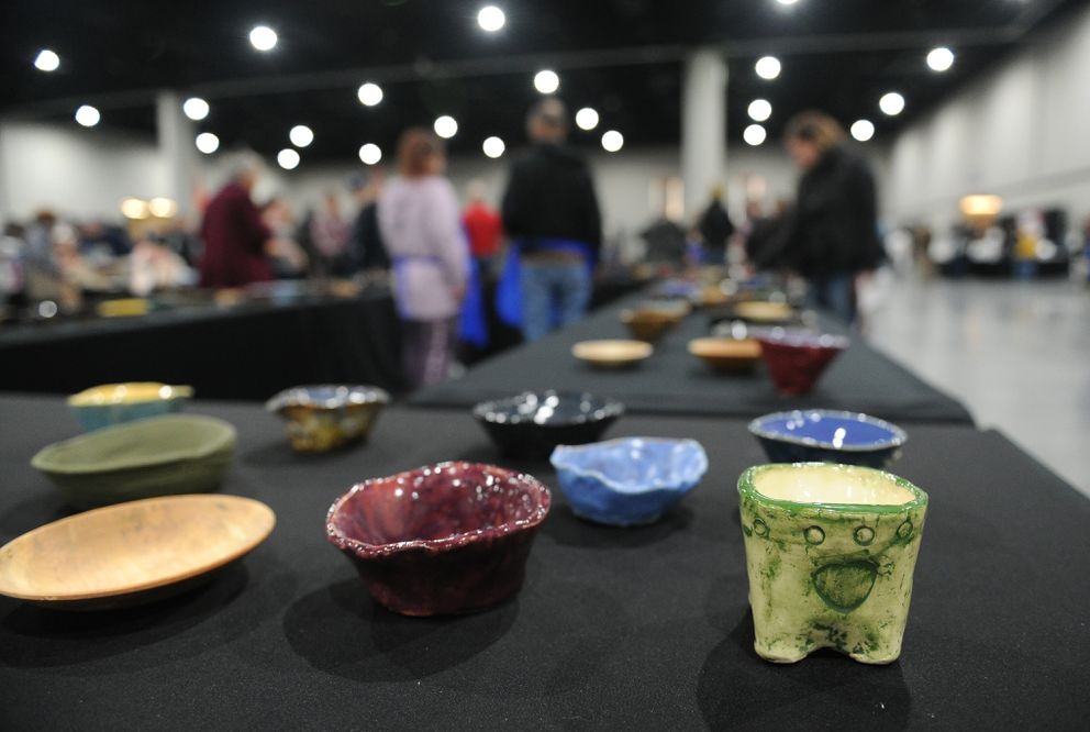 People choose a bowl during the Empty Bowl Project at the Dena'ina Center. (Bob Hallinen / ADN)