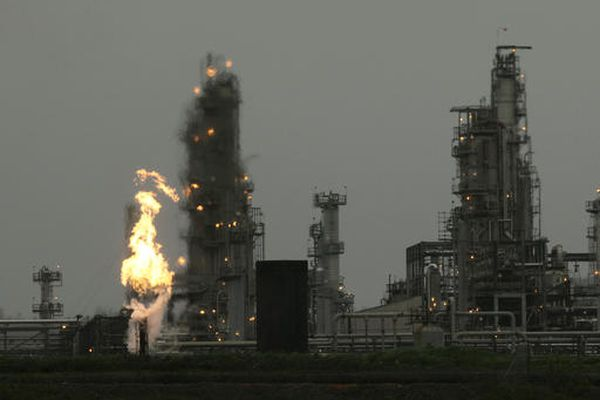 FILE - In this April 2, 2010, file photo, a Tesoro Corp. refinery, including a gas flare flame that is part of normal plant of operations, is shown in Anacortes, Wash., after an overnight fire and explosion at the refinery killed three people and critically injured four others who were working at the plant. Federal investigators have issued new safety recommendations aimed at preventing accidents similar to the 2010 explosion. (AP Photo/Ted S. Warren, File)