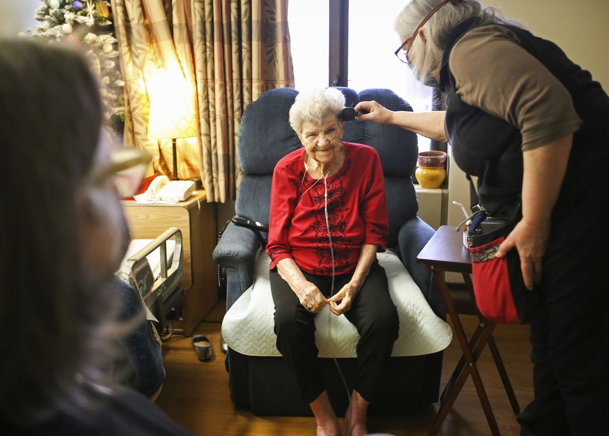 Kim Kiml brushes her mother's hair while she and her sister, Winter Wolf, visit her at the Pioneer Home in Anchorage on Wednesday, Feb. 3, 2021. Their mother, Ellie Brimanis, hasn't been allowed to have visitors since mid-March due to pandemic restrictions. (Emily Mesner / ADN)