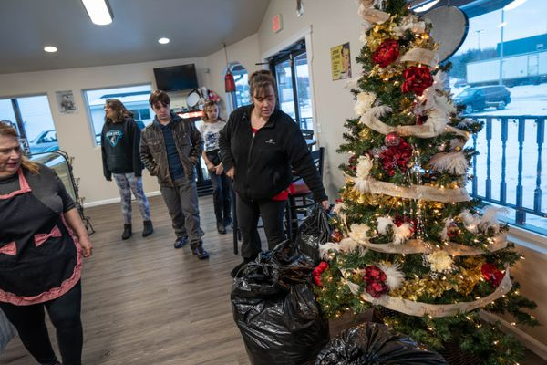 Lauren McIver-O'Hara picks up bags of donations from Triple J Roadhouse on Wednesday, Dec. 23, 2020 in Wasilla. McIver-O'Hara and her family drove into their Big Lake home last Friday evening to find it burning. They lost the home and 17 pets. Triple J Roadhouse owner Jessica Briles, at left, has been collecting donations for the family. With McIver-O'Hara are her three children, Scarlett O'Hara, 17, Sabella McIver-O'Hara, 10, and Sean O'Hara, 15. McIver-O'Hara's husband Robert McIver has been in the hospital with Covid-19 since Dec. 11. (Loren Holmes / ADN)