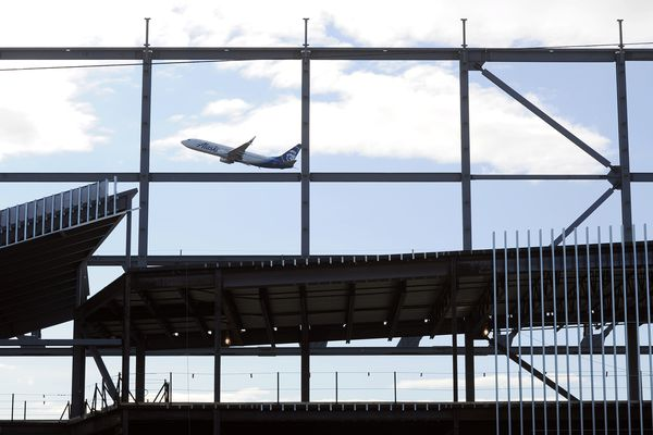 An Alaska Airlines jet takes off past a new maintenance hangar the airline is building along Old International Airport Road on Friday, September 15, 2017, at Ted Stevens Anchorage International Airport. The $50-million project was designed by McCool Carlson Green, with Kiewit serving as general contractor. The 105,000-square-foot building is slated for completion in the spring of 2018. (Erik Hill / Alaska Dispatch News)