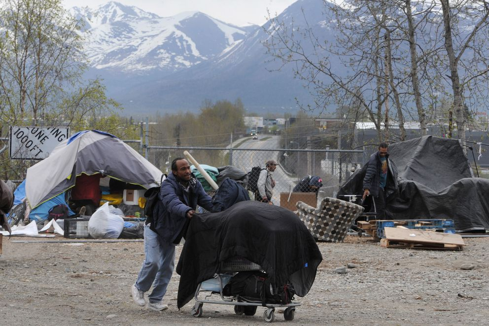 Myron Traylor pushes his belongings in a shopping cart as Anchorage Police and Parks and Recreation workers removed an illegal homeless campsite near 3rd Avenue and Ingra Street on Monday, May 11, 2020. (Bill Roth / ADN)