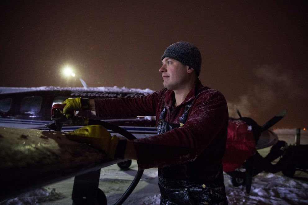 Matt Gallagher, a pilot for Warbelow's Air, adds fuel to the airplane in subzero temperatures before taking off for a flight to Beaver at the airport in Fairbanks on Dec. 2. Gallagher plans to leave Alaska for a job with a larger commercial company Outside. (Ruth Fremson/The New York Times)