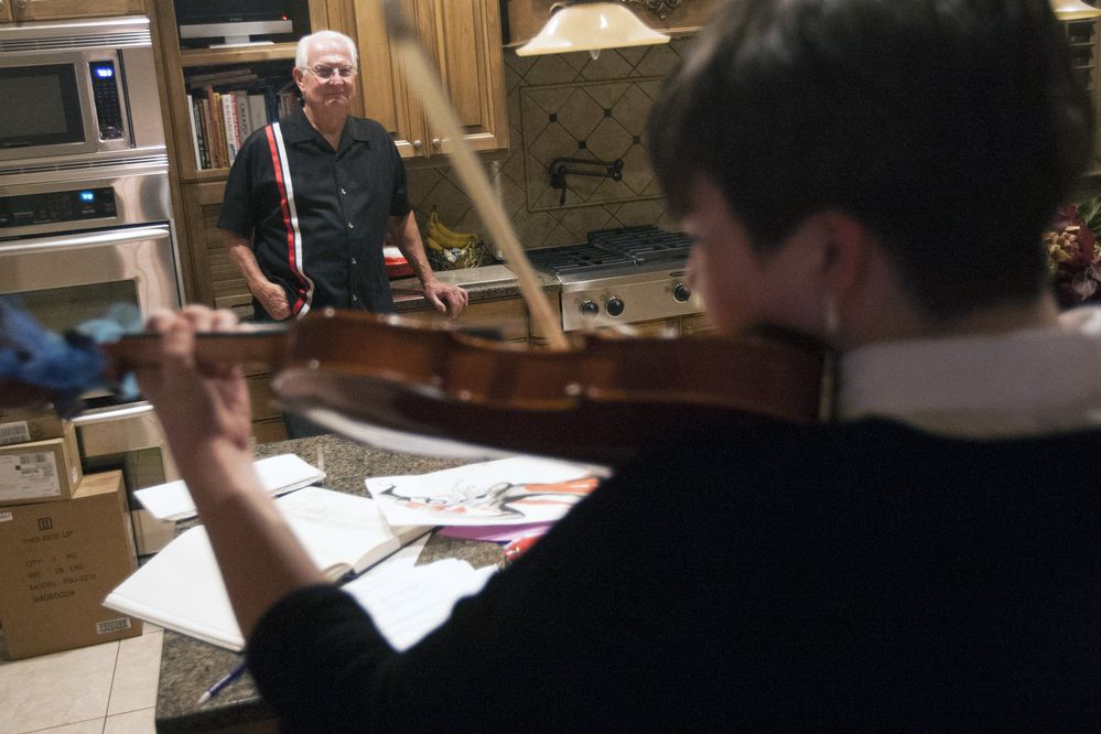 In this Wednesday, Oct. 22, 2014 photo, Bill Pendleton watches Audrey Pendleton, 15, play the violin at their home in Draper, Utah. The Pendletons are among a growing number of families across the country that find grandparents raising their grandchildren, with varying or no participation from the children's parents. (AP Photo/The Deseret News, Michelle Tessier) SALT LAKE TRIBUNE OUT; MAGS OUT