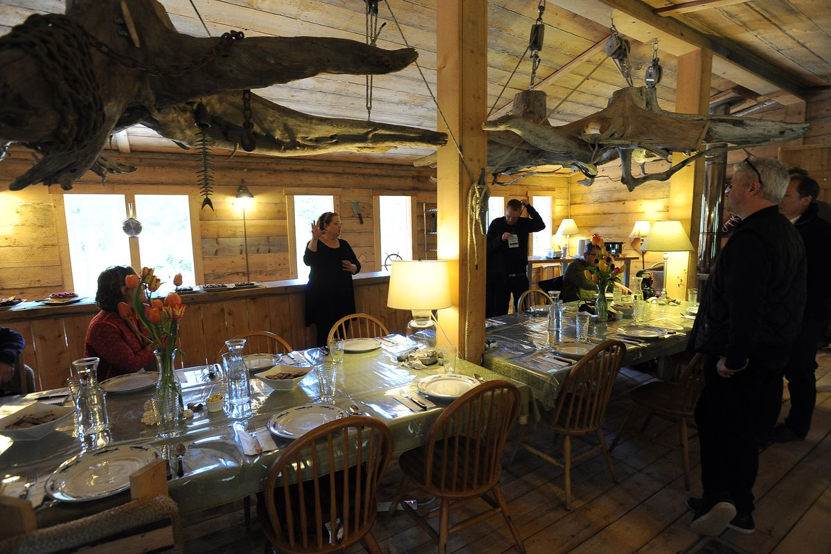 Striking decor greets visitors to the dining room in the Widgeon II, which hosts cooking classes at the Tutka Bay Lodge. The beached vessel is a repurposed crabbing boat that wasoriginally a World War II-era troop carrier. Owner Kirsten Dixon, center, describes the facility to visiting Norwegian journalists in2015. (Erik Hill / Alaska Dispatch News)