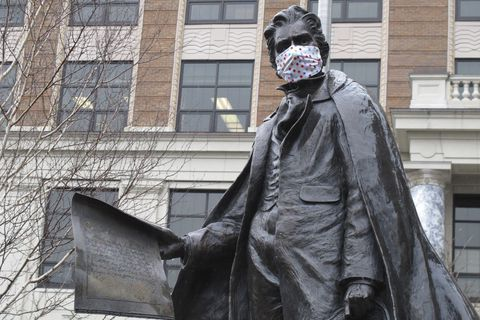 A statue of William Seward near the Alaska Capitol is shown outfitted with a mask on Friday, April 24, 2020, in Juneau, Alaska. On Friday, the state began allowing restaurants to resume dine-in service and retail shops and other businesses to reopen, all with limitations, under an initial phase of a plan to restart parts of the economy affected by coronavirus concerns. (AP Photo/Becky Bohrer)
