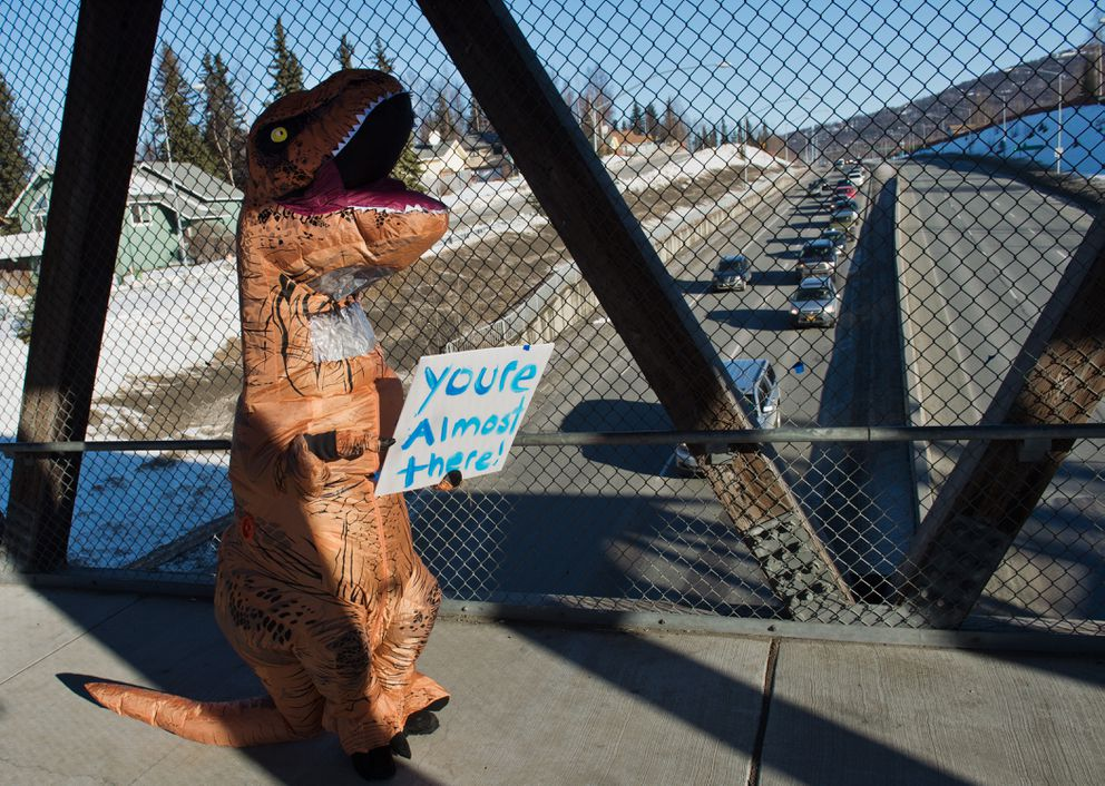 "Theresa Bundy wore a dinosaur costume and held a sign that said ""You're almost there"" to backed-up traffic from a pedestrian bridge over Eagle River Loop Road. ""Just easing the tension,"" Bundy said. Traffic was backed up on Eagle River Loop Road after the Glenn Highway was closed to inbound vehicles on Thursday. (Marc Lester / ADN)"