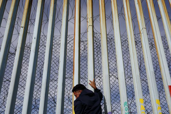 A man holds on to the border wall along the beach, Tuesday, Jan. 8, 2019, in Tijuana, Mexico. Ready to make his case on prime-time TV, President Donald Trump is stressing humanitarian as well as security concerns at the U.S.-Mexico border as he tries to convince America he must get funding for his long-promised border wall before ending a partial government shutdown that has hundreds of thousands of federal workers facing missed paychecks. (AP Photo/Gregory Bull)
