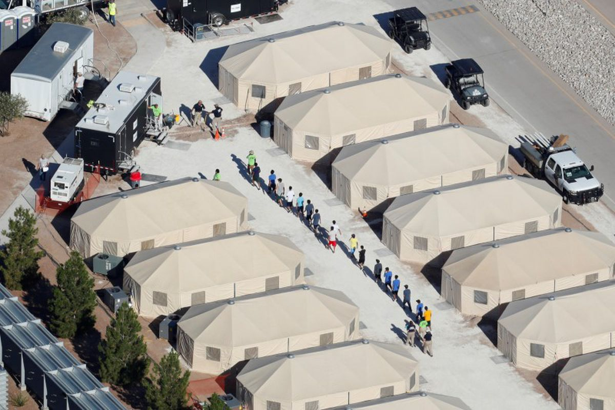 """Immigrant children now housed in a tent encampment under the new """"zero tolerance"""" policy by the Trump administration are shown walking in single file at the facility near the Mexican border in Tornillo, Texas. REUTERS/Mike Blake"""