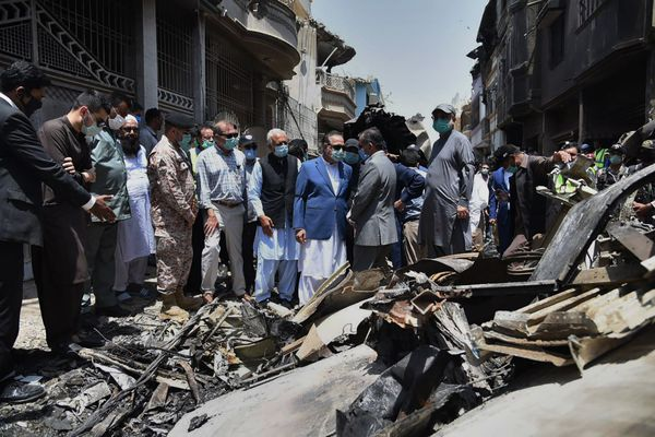In this photo released by Pakistan Civil Aviation Authority, provincial governor Imran Ismail, center, in blue coat, and Pakistan's aviation minister Ghulam Sarwar, center in black waistcoat, visit the site of Friday's plane crash, in Karachi, Pakistan, Saturday, May 23, 2020. Apassenger plane belonging to state-run Pakistan International Airlines carrying passengers and crew crashed near the southern port city of Karachi on Friday. (Pakistan Civil Aviation Authority, via AP)