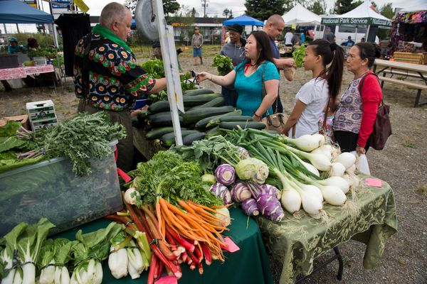 Bob Shumaker, of Black Bear Farms in Palmer, makes a sale. The Mountain View Farmers Market, in its first year, operates on Thursdays through August along Mountain View Drive. It's hosted by Anchorage Community Land Trust. (Marc Lester / Alaska Dispatch News)