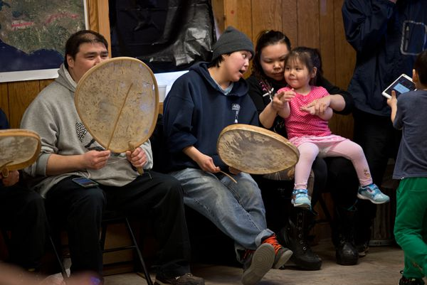 Britany Kava, center, sings to a youngster on Rosina Toolie's lap. (Marc Lester / Alaska Dispatch News)
