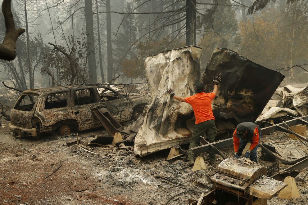 Search and rescue workers search for human remains at a burned out trailer park from the Camp fire, Tuesday, Nov. 13, 2018, in Paradise, Calif. (AP Photo/John Locher)